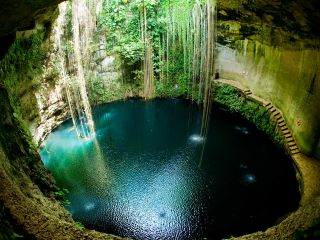A Large cenote in A Forest With Chichen Itza In The Background